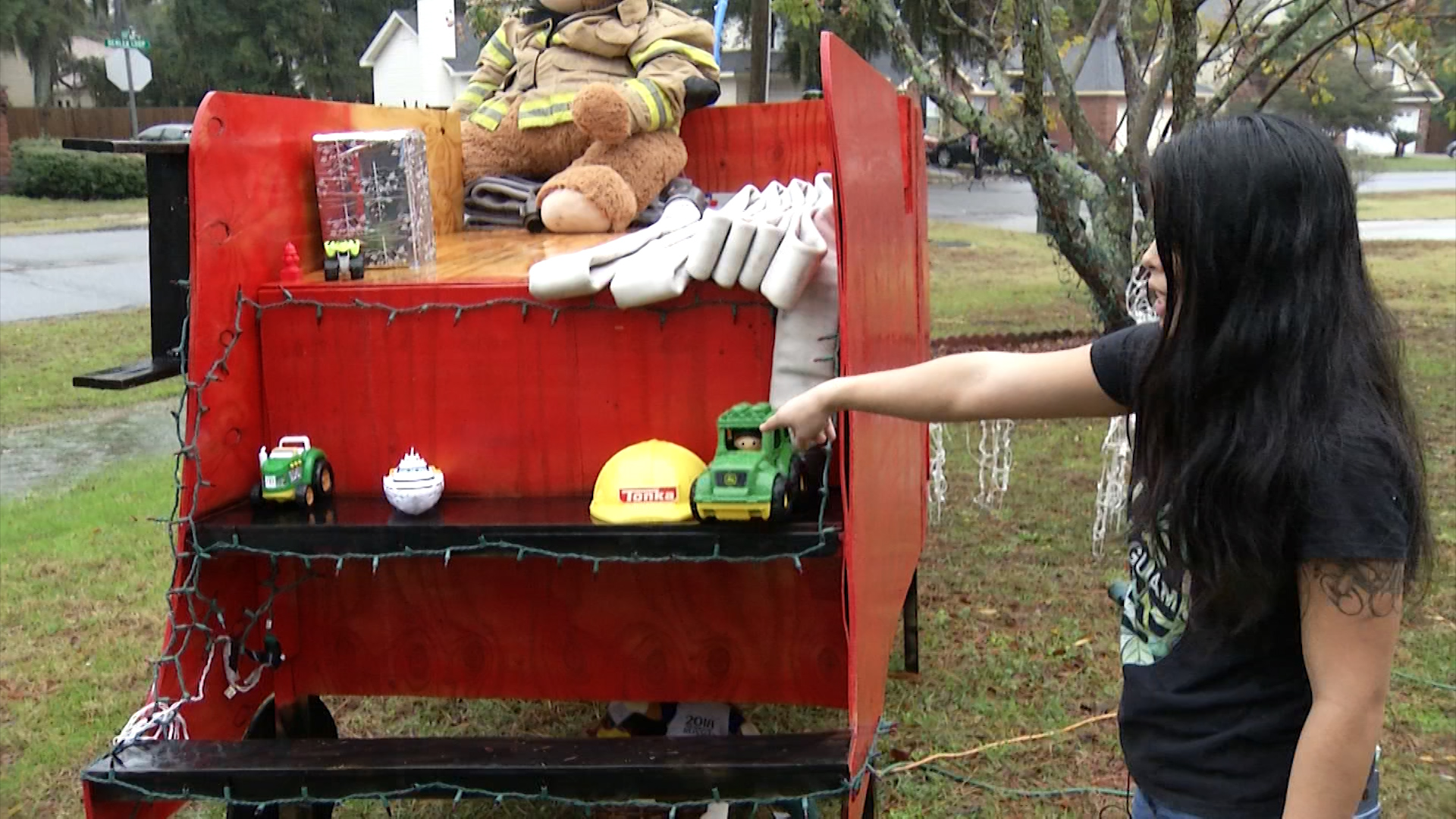 Joan Thompson collects toys in her front yard for needy families.